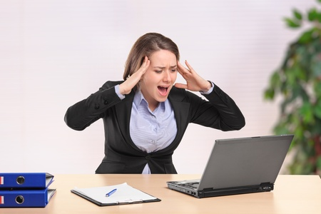 A nervous young businesswoman yelling to a laptop in the office Stock Photo - 9825808
