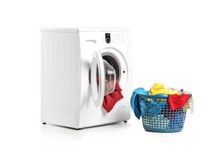 A washing machine and full laundry bin isolated on white background Stock Photo - 9822829