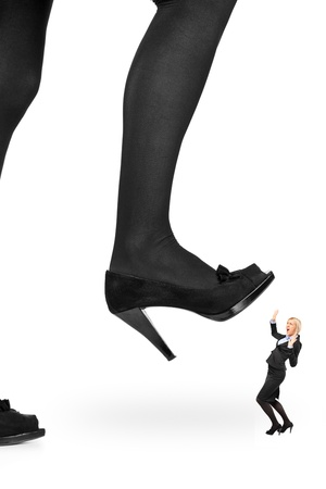 trample: Big woman shoe stepping on a businesswoman isolated on white background