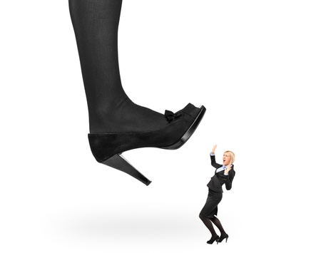 trample: Big woman shoe stepping on an affaraid businesswoman isolated on white background