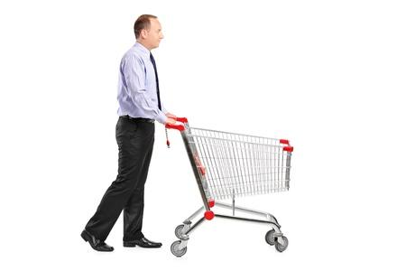 carretilla de mano: Un retrato de toda la longitud de un hombre empujando un carrito de compras vacío aislado en fondo blanco