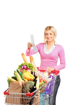 A smiling woman checking her shopping receipt isolated on white background photo