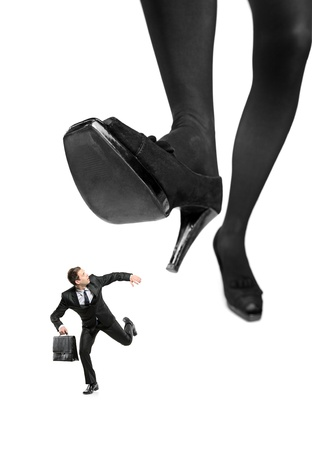 Afraid businessman running away from a big foot isolated on white background photo