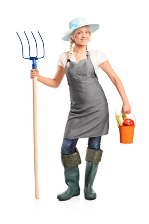 hayfork: Full length portrait of a female farmer holding a pitchfork and bucket with vegetables isolated on white background Stock Photo