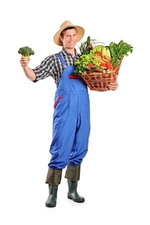 agricultor: Retrato de longitud completa de un granjero hombre sosteniendo una cesta llena de verduras aisladas sobre fondo blanco