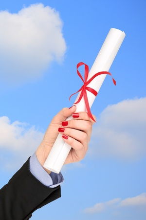 Woman holding a diploma with a red ribbon photo