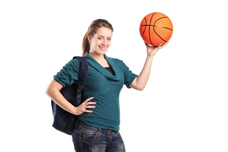 Young school girl holding a basketball isolated on white background photo