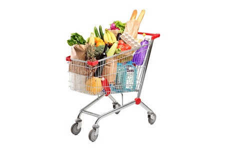 carts: A shopping cart full with various groceries isolated on white background