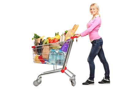 A young female pushing a shopping cart full with groceries isolated on white background Stock Photo - 9997241