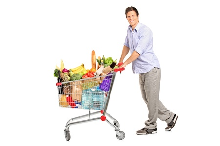 grocery cart: A young male pushing a shopping cart full with groceries isolated on white background Stock Photo