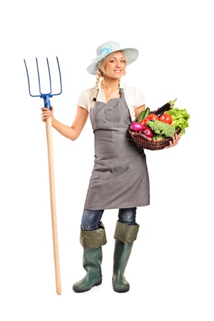 Full length portrait of a female farmer holding a pitchfork and basket with vegetables isolated against white background photo