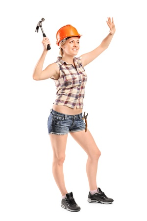 Full length portrait of a female manual worker with hammer isolated against white background photo