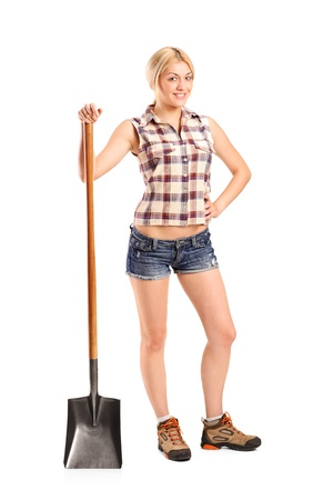 Full length portrait of a female worker holding a shovel isolated on white background photo