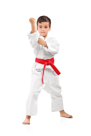 karate kick: Full length portrait of a karate kid posing isolated on white background Stock Photo