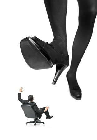 agitated: A giant foot about to squish a businessman in a chair isolated on white background