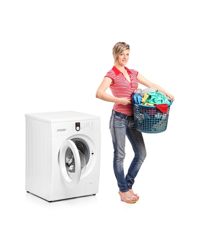 dirty clothes: Full length portrait of a woman holding a basket and standing next to a washing machine isolated on white background