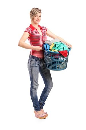 lavadora con ropa: Retrato de longitud completa de una joven mujer sosteniendo una canasta de lavandería aislada sobre fondo blanco Foto de archivo