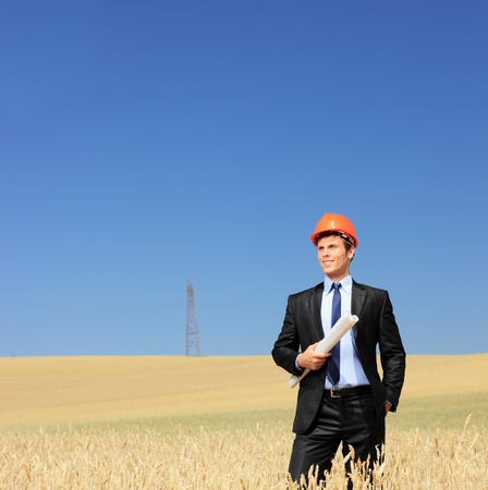 Young foreman wearing protective helmet and holding blueprints in a wheat field photo