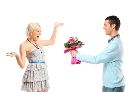 Boyfriend giving flowers to his surprised girlfriend isolated against white background photo