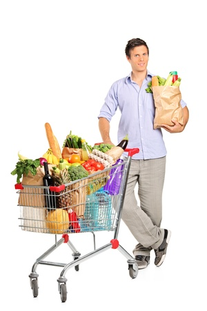 Full length portrait of a man with paper bag next to a shopping cart full with groceries isolated on white background photo