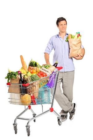 carretilla de mano: Retrato de cuerpo entero de un hombre con una bolsa de papel junto a un carrito lleno de comestibles aisladas sobre fondo blanco Foto de archivo