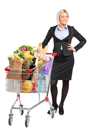 full shopping cart: Full length portrait of a young woman posing next to a shopping cart full with groceries isolated on white background