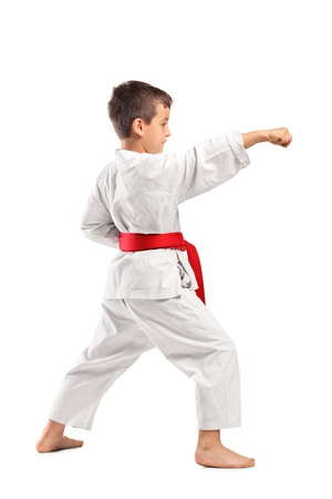 Full length portrait of a karate child posing isolated against white background photo
