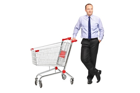 Full length portrait of a man posing next to an empty shopping cart isolated on white background