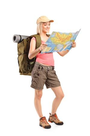 sportwear: Full length portrait of female hiker looking at map isolated on white background
