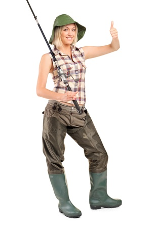 waders: Full length portrait of a smiling fisherwoman with thumb up isolated on white background