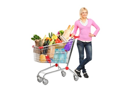 Full length portrait of a young woman posing next to a shopping cart isolated on white background