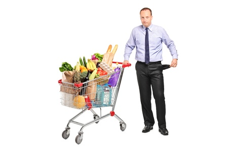 Bankrupt man holding a shopping cart and gesturing no more money isolated on white background photo