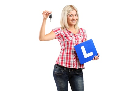 Happy teenager holding a car key and L plate isolated on white background photo