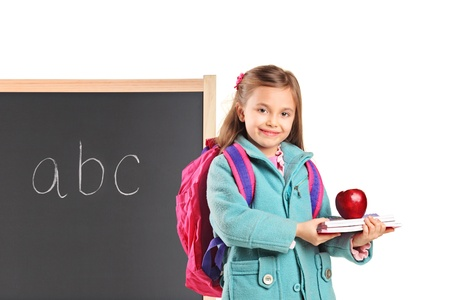 A school girl with backpack holding notebooks and an apple isolated on white background photo