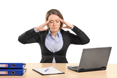 overloaded: A young businesswoman in pain as a result of a headache posing isolated on white background