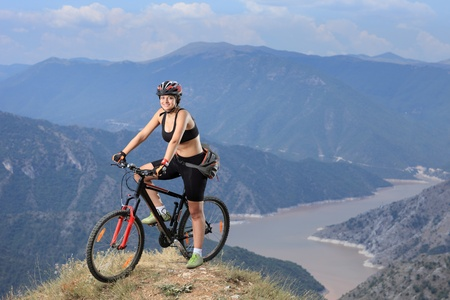 A young female posing with a mountain bike with lake in the background photo
