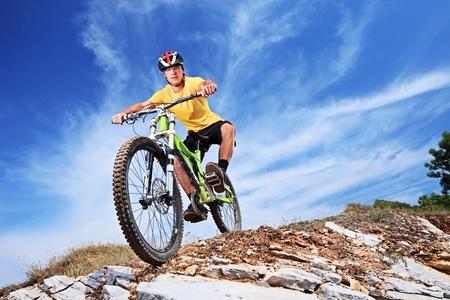 montando bicicleta: Un joven montando una bicicleta de monta�a al aire libre