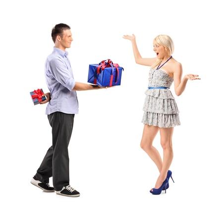 dar un regalo: Retrato de longitud completa de un macho dando un regalo a su novia emocionada aislada sobre fondo blanco