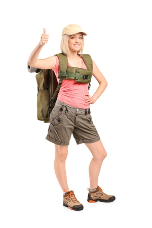 backpackers: Full length portrait of a smiling woman with backpack givimh thumb up isolated on white background