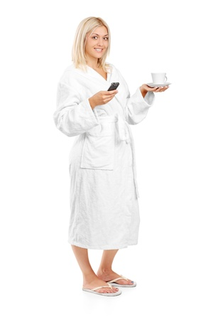 Full length portrait of a young woman in bathrobe holding a coffee cup and mobile phone isolated on white background photo
