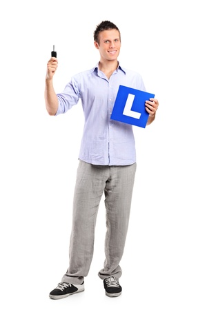 Happy man holding a car key and L plate isolated on white background photo