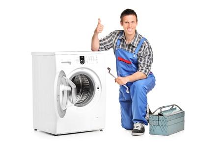 launder: Un reparador sosteniendo una llave y renunciar a pulgar junto a una lavadora aislada sobre fondo blanco Foto de archivo