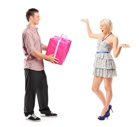 dar un regalo: Retrato de longitud completa de un novio sosteniendo un regalo y su novia emocionada aisladas sobre fondo blanco
