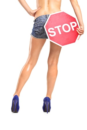 A view of an attractive woman holding a traffic sign stop over her buttock isolated on white background photo