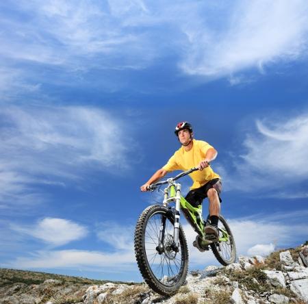 montando bicicleta: Un hombre joven montando una bicicleta de monta�a al aire libre
