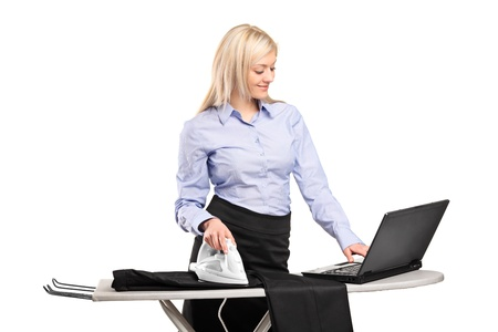 workaholic: Blond businesswoman ironing his clothes and working on a laptop isolated on white background Stock Photo