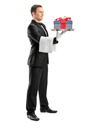 Full length portrait of a butler with bow tie carrying a tray with gift on it isolated against white background Stock Photo - 10453699