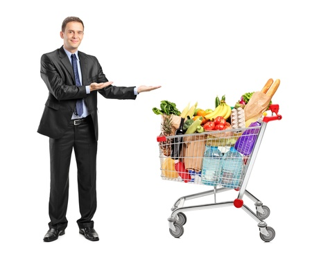 Full length portrait of a man in suit gesturing and shopping cart isolated on white background Stock Photo - 10453718