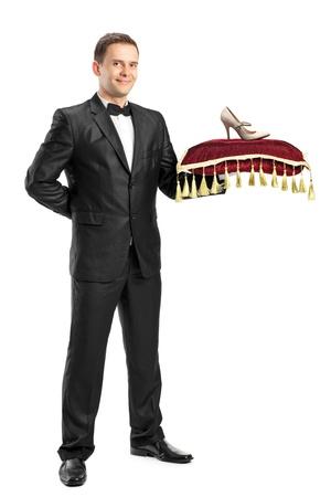 sirvientes: Retrato de longitud completa de un hombre con traje sosteniendo una almohada con un azadón en él aisladas sobre fondo blanco