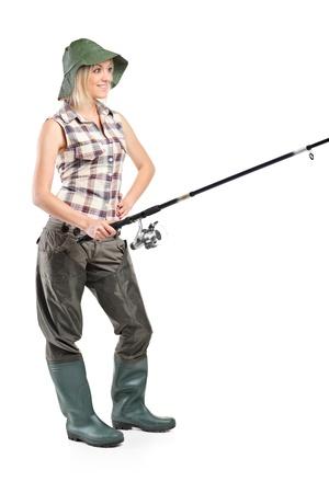 botas altas: Retrato de longitud completa de una mujer sosteniendo un polo de pesca aislado sobre fondo blanco